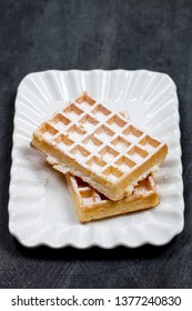 Belgium waffers with sugar powder on ceramic plateon black board background. Fresh baked wafers.