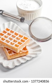 Belgium waffers with sugar powder on ceramic plate and strainer on white table. Fresh baked wafers.