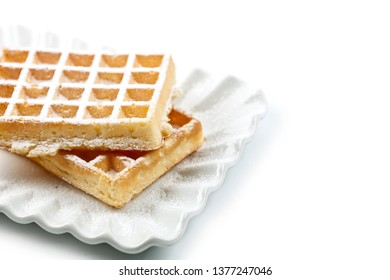 Belgium waffers with sugar powder on ceramic plate isolated on white background. Fresh baked wafers. With copy space.