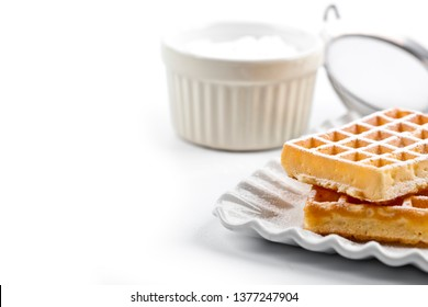 Belgium waffers with sugar powder on ceramic plate and strainer on white table. Fresh baked wafers closeup on white background with copy space..