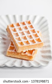 Belgium waffers with sugar powder on ceramic plate isolated on white background. Fresh baked wafers.