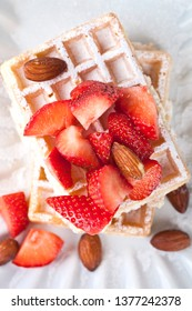 Belgium waffers with sugar powder, strawberries, almonds and chocolate on white ceramic plate. Fresh baked wafers. Top view.
