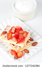 Belgium waffers with sugar powder, strawberries and almonds on ceramic plate on white table. Fresh baked wafers.