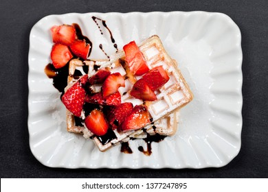 Belgium waffers with sugar powder, strawberries and chocolate on ceramic plate on black board background. Fresh baked wafers top view.