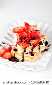 Belgium waffers with sugar powder, strawberries and chocolate on ceramic plate on white table. Fresh baked wafers.