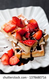 Belgium waffers with sugar powder, strawberries and chocolate on ceramic plate on black board background. Fresh baked wafers.