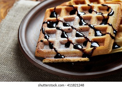 belgium waffles with chocolate topping and sugar powder. On a rustic background with sacking cloth.