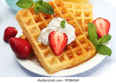 belgium waffles with honey, strawberries and mint on plate isolated on white