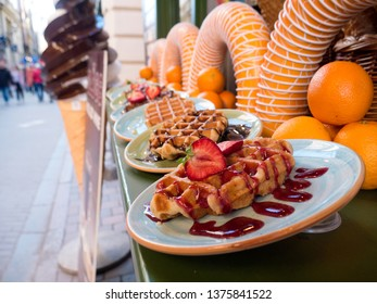 Belgium waffles with strawberry and oranges at street display