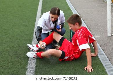 BELGOROD, RUSSIA - AUGUST 20: Unidentified nurse helps to  unidentified boy on football field on August, 20 2010 in Belgorod, Russia. The final of Chernozemje superiority, team of 1996 year of birth.