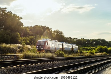 Belgorod, Russia - June 12, 2017: Suburban rail bus RA2 on the rail road. Diesel train of Russian railways. Commuter passenger red train goes towards on a track railroad in evening backlight sunlight.