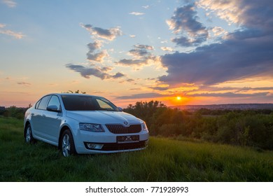Belgorod, Russia - May 9, 2016: White Skoda Octavia. A beautiful sunset by the river, a view from the mountain, on the banks of a juicy green grass. The sky was painted in bright colors.