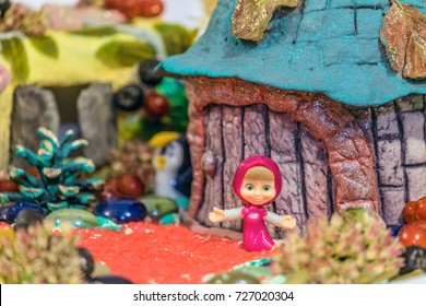 Belgorod, Russia - September 19, 2017: Figurine of character Masha from popular cartoon about Masha and the Bear in hand-made crafts scenery. Limited depth of field.