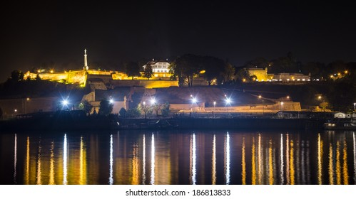 Belgrade fortress Kalemegdan and the monument of Victor in the night time with the port on river Sava below with reflecting lights in the river