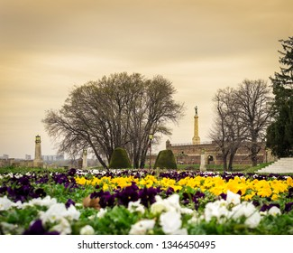 Belgrade, Serbia - 03 20 2019: Famous The Victor (Pobednik) monument in the background and foreground colorful flowers low perspective shot on Kalemegden fortress in Belgrade during golden hour