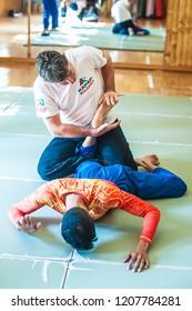 BELGRADE, SERBIA – 04 -12. OCTOBER 2018. Instructor and Students practice BJJ Brazilian jiu-jitsu technique training on the AVI NARDIA KAPAP SELF DEFENSE SEMINAR