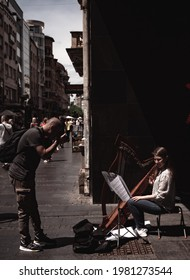 Belgrade, Serbia.  05.22.2021.  Photographer taking picture of a girl playing harp on a city sidewalk, public performance tourist photo.
