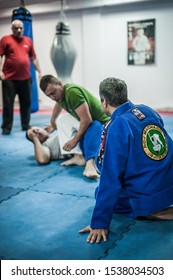 BELGRADE, SERBIA - 13. OCTOBER 2019. Sensei master Avi Nardia in traditional kimono, demonstrate BJJ Brazilian jiu-jitsu ground control and finish technique to his students on Kapap Krav Maga seminar