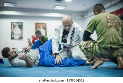 BELGRADE, SERBIA - 13. OCTOBER 2019. Sensei master Igor Sucevic in traditional kimono, demonstrate BJJ Brazilian jiu-jitsu ground control and finish technique to his students on Kapap Krav Maga semina