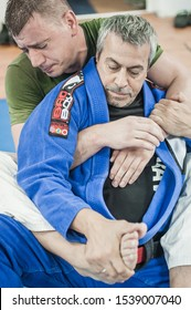 BELGRADE, SERBIA - 13. OCTOBER 2019. Sensei master Avi Nardia in traditional kimono, demonstrate BJJ Brazilian jiu-jitsu leg lock and escape technique to his students on Kapap Krav Maga seminar
