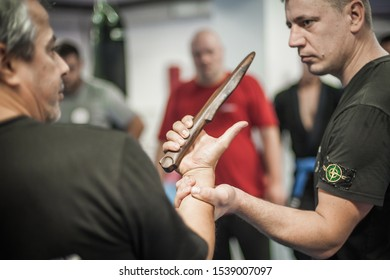 BELGRADE, SERBIA - 13. OCTOBER 2019. Kapap Krav Maga Sensei master instructor Avi Nardia demonstrates combat knife attack self-defense technique to large group of students on Kapap Krav Maga seminar