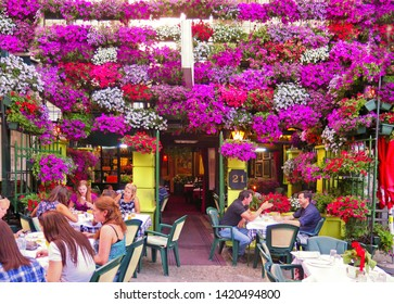 BELGRADE, Serbia 15.06.2018. Tourists enjoy in restaurant outside garden tables in Skandarlija (Skandarska), Belgrade's bohemian quarter with colorful flower in background.