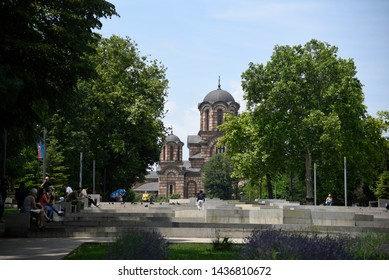 BELGRADE, SERBIA - 17 JUNE 2019: People enjoy hot summer day in Tasmajdan park sittng on benches under trees, with a view of Saint Marks church