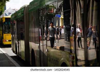 BELGRADE, SERBIA - 24 JUNE 2019: Pedestrian's reflection in the parked bus windows. Every summer Belgrade cuts number of public transport buses