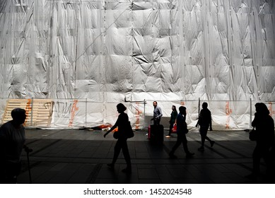 BELGRADE, SERBIA - 24 JUNE 2019: Silhouette of people, passing by covered building under construction