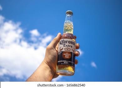 """BELGRADE SERBIA 26 02 2020 Corona beer bottle in the hand. Corona Brewery. Hand holding bottle of Corona Extra Beer.  """"La cerverza mas fina.""""  One of the best beer products in global drink industry."""