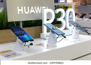 Belgrade, Serbia - April 05, 2019: New Huawei P30 mobile smartphones are shown on retail display in electronic store. Huawei and P30 logo in the background.