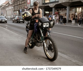 Belgrade, Serbia Aug 29, 2019: Urban scene with a young man sitting on a motorbike parked at a sidewalk