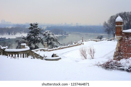 Belgrade, Serbia. Cityscape with snowfall in Kalemegdan fortress and castle completely covered by snow in winter blizzard with Danube river in background .