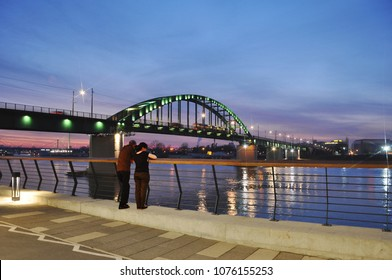 BELGRADE, SERBIA - DECEMBER 02, 2016. Sava promenade and Old Sava Bridge that connects the old part of the city and New Belgrade. Two people enjoy the sunset over Belgrade.