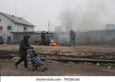 Belgrade, Serbia - December 19, 2016: Migrants gathered in front of an abandoned house. Around 2000 migrants, mostly men from Afghanistan and Pakistan spent the freezing winter in abandoned warehouse.