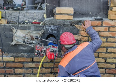 BELGRADE, SERBIA - DECEMBER 24: Wet coring work,  drilling penetration on concrete wall for pipe. Selective focus. At construction site in December 2014.