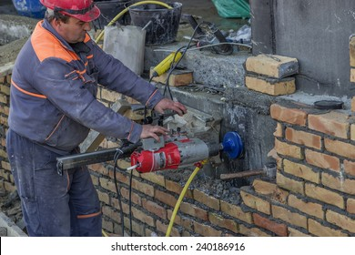BELGRADE, SERBIA - DECEMBER 24: Worker with core drill, drilling penetration on concrete wall for pipe. Selective focus. At construction site in December 2014.