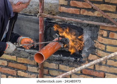 BELGRADE, SERBIA - DECEMBER 26: Insulation worker with propane blow torch melting bitumen felt around pipe on the basement wall. At construction site in December 2014.