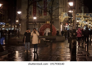 BELGRADE, SERBIA - DECEMBER 27, 2020 Two young women, friends, talking pictures and shooting with their smartphone mobile phone on kneza mihalova street, the main pedestrian street of Belgrade.