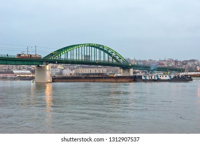 Belgrade, Serbia - February 10, 2019: Old railway bridge, a ship under the bridge and a tram on the bridge.