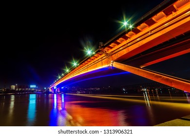 Belgrade, Serbia - February 10, 2019: The Gazela Bridge (Serbian: Most Gazela) is the most important bridge over the Sava river in Belgrade. A panorama of Belgrade by night with reflection in water.