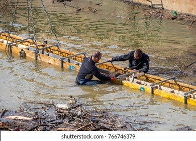 BELGRADE, SERBIA - FEBRUARY 24, 2017: Two divers install concrete form work in water for river bank repair, phase of Belgrade Waterfront project. Concrete revetment.