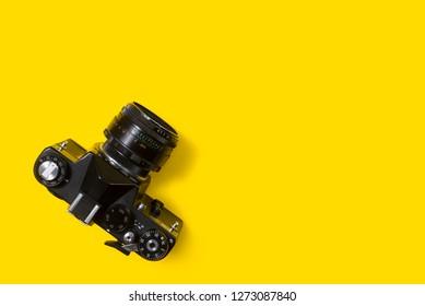 BELGRADE, SERBIA , JANUARY 02 2019: Top view of vintage 35mm film camera on yellow background. Retro camera from above on yellow background