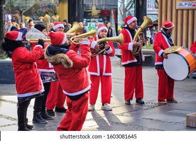 Belgrade / Serbia - January 1, 2020: Brass trumpet band musicians dressed in Santa Claus costumes performing on New Year's Day in pedestrian Knez Mihailova street in central Belgrade, Serbia