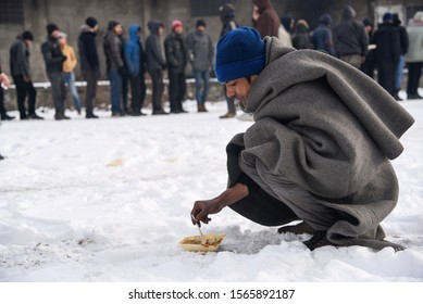 BELGRADE, SERBIA - JANUARY 12, 2017: Migrant taking a lunch. Around 2000 migrants, mostly men from Afghanistan and Pakistan spent the freezing winter in abandoned warehouses.