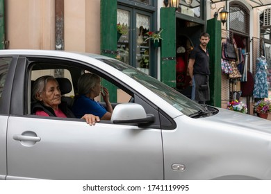 Belgrade, Serbia, Jul 13, 2019: Urban scene with two women sitting in a car parked next to the pub