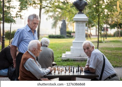 BELGRADE, SERBIA - JULY 11, 2018: Old senior men playing chess in a park of Kalemegdan fortress, in Belgrade, Serbia. Kalemegdan is one of the main landmarks of the city.