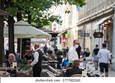 BELGRADE, SERBIA - JULY 12, 2020: Waiter, a server in uniform, working at the terrace of a cafe serving food to clients wearing a respiratory face mask during the coronavirus covid 19 health crisis.