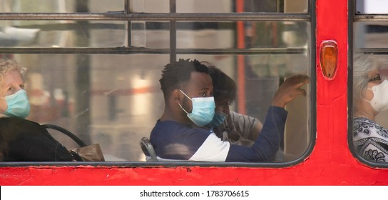 Belgrade, Serbia - July 16, 2020: Young black man wearing surgical face masks while sitting and riding on a window seat of a tram