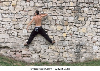 BELGRADE, SERBIA - JULY 19, 2018: rear view muscular fit topless of young man is training urban climbing on a vertical wall of Kalemegdan Fortress